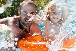 Father and child playing in water