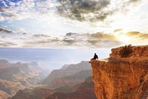 man admiring view from cliff